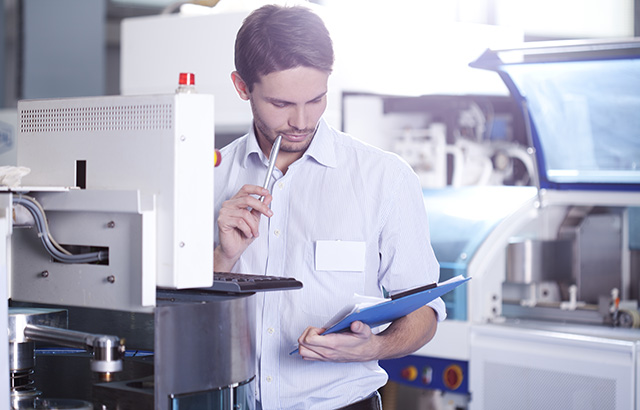 Engineering Worker in Shop on Computer Holding Pen and Paper